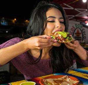 woman eating tostada